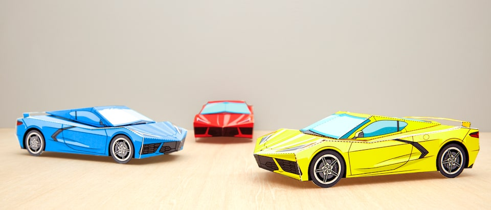 Three assembled paper models of the 2020 Corvette in red, yellow,  and blue.