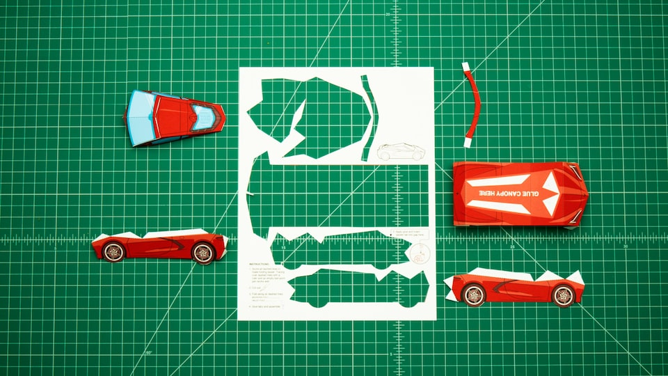 The paper template for the 2020 Corvette model sits on a green artist's board with the individual pieces cut out and lying on the board. The accompanying video shows the assembly.