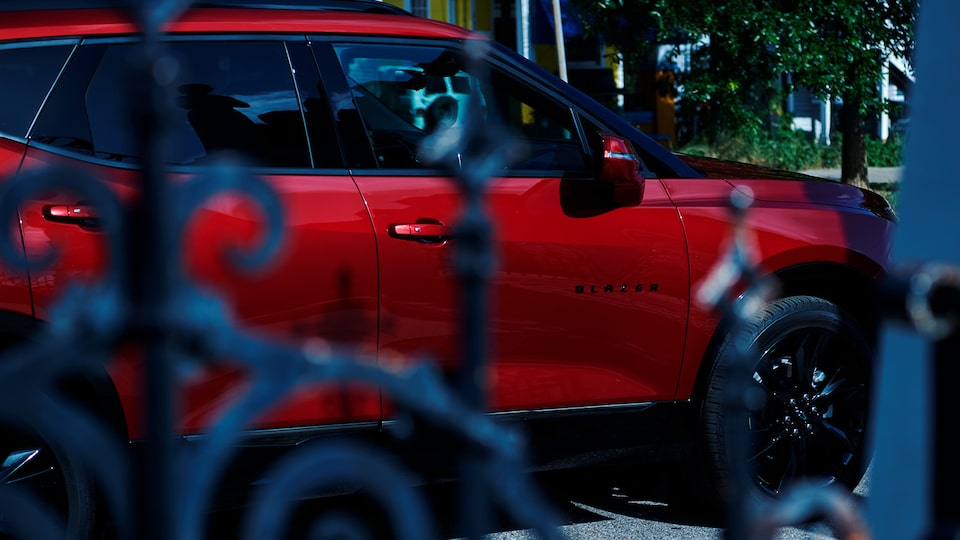 A red Chevy Blazer is seen through a wrought iron gate.