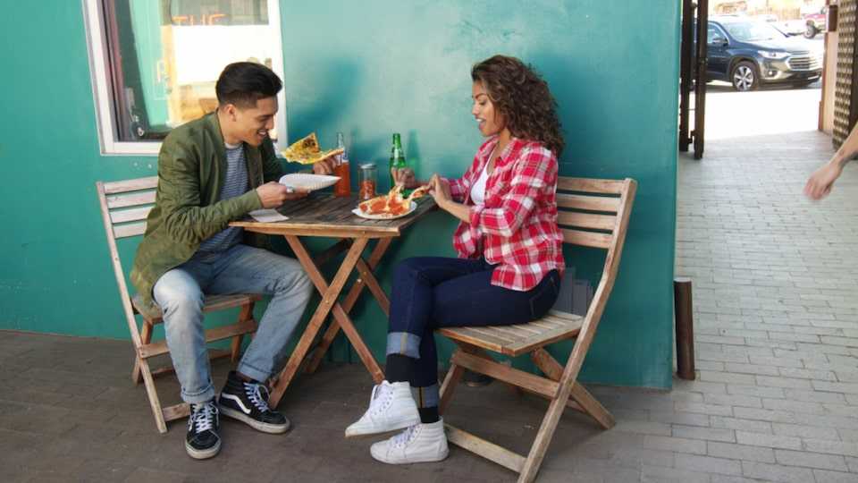 A young man and woman sit on folding chairs at a small table in an open-air restaurant eating pizza.