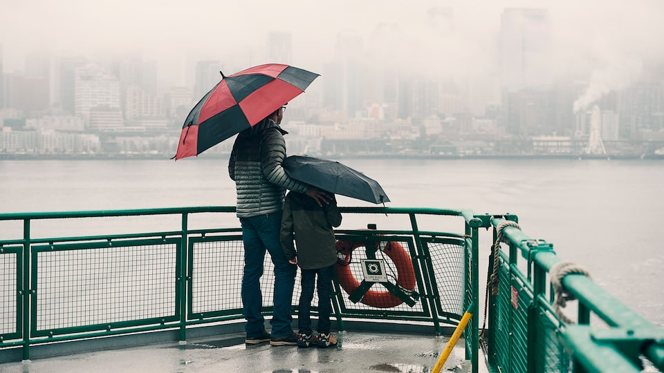 A father and son stand on the deck of a car ferry in the rain, holding umberalls and looking out at Seattle.