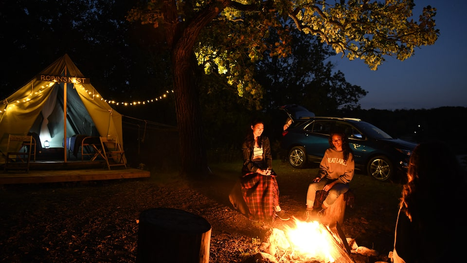 Three friends sit around a bonfire at night with a Chevrolet Equinox in the background.