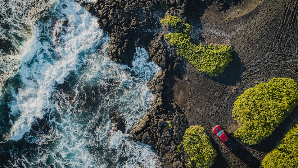 An aerial shot of a red Chevrolet Colorado ZR2 parked near the edge of a rocky landscape with water rushing past.