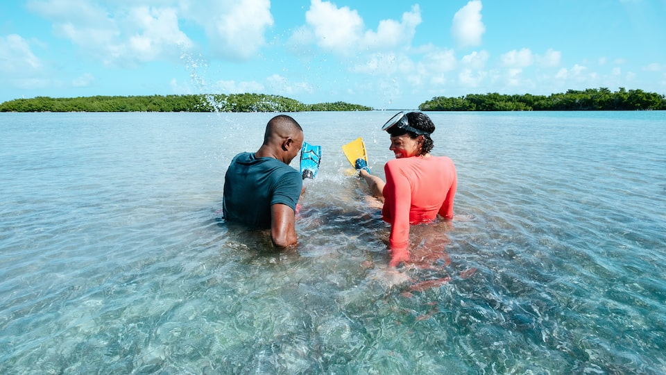 A man and woman wearing swim flippers sit in shallow ocean water with islands in the background.