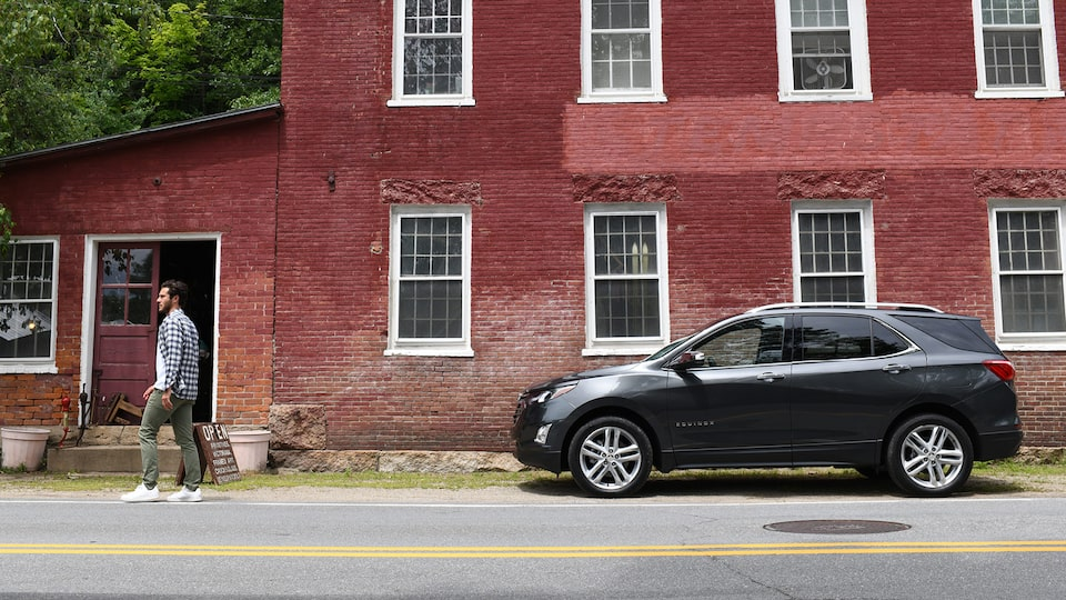 A Nightfall Gray Metallic Chevrolet Equinox sits on a street outside an old red brick two-story building. A man is walking down the street away from the Equinox.