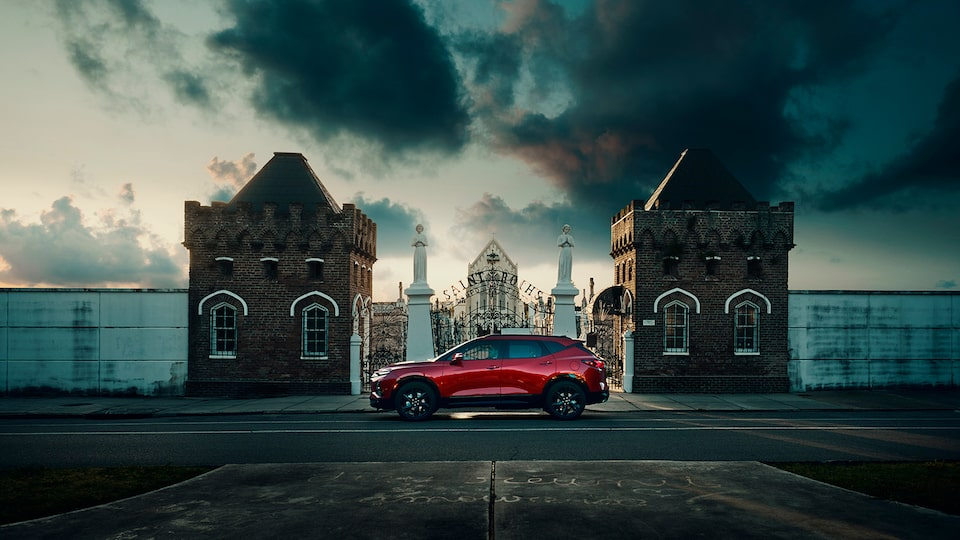 A red Chevy Blazer seen in profile on a street in front of a wrought iron gate between two large brick pillars with a cemetery in the background and dark clouds overhead.