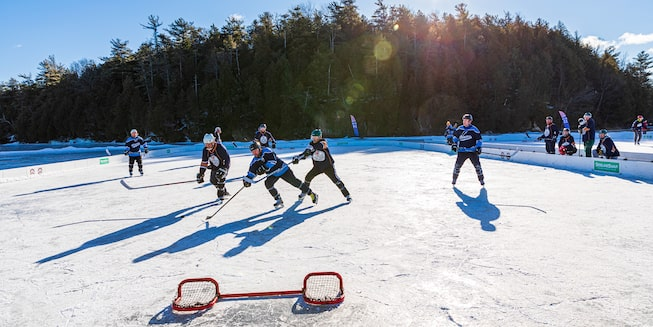 A group of people playing hockey on a frozen pond with a short goal net in the foreground and trees in the background.