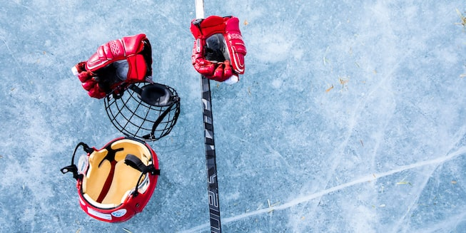 A pair of hockey gloves, a helmet, face protection, and a stick sit on the ice.
