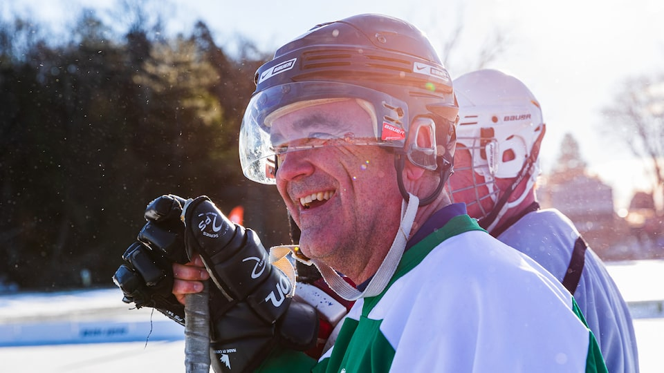 A man in a hockey helmet and gloves holding a hockey stick smiles.