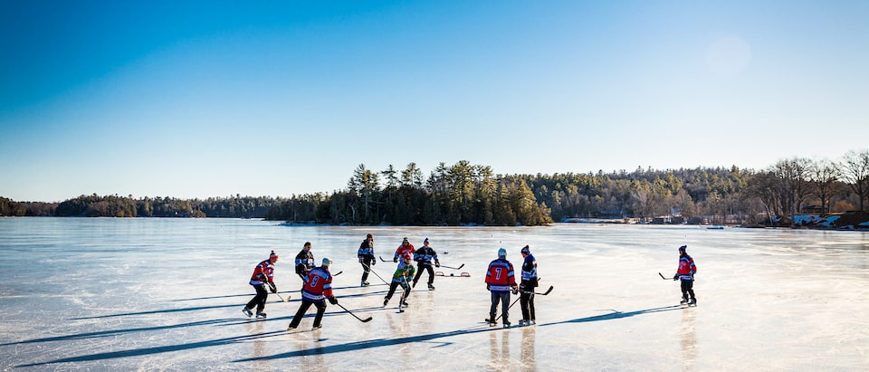 A group of people playing hockey on a frozen pond with a clear blue sky and trees in the background.