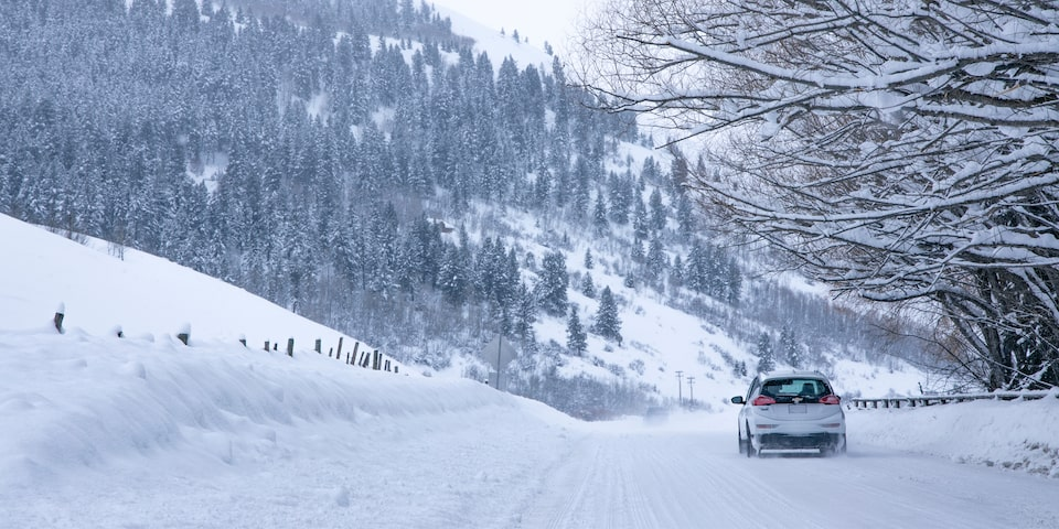 A white Bolt EV is seen from behind as it drives down a snow-covered hill surrounded by snowy trees.