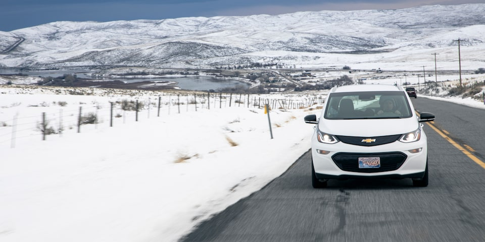 A white Bolt EV drives along a clear road with snow along the roadside and snow-covered hills in the background.