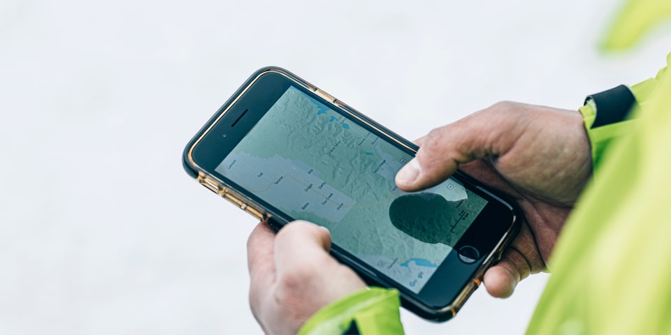 A man wearing a neon green jacket is holding a smartphone and tapping the screen.