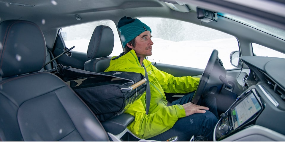 Greg Hill, wearing a neon green jacket and turquoise cap, sits in the driver's seat of a white Bolt EV.