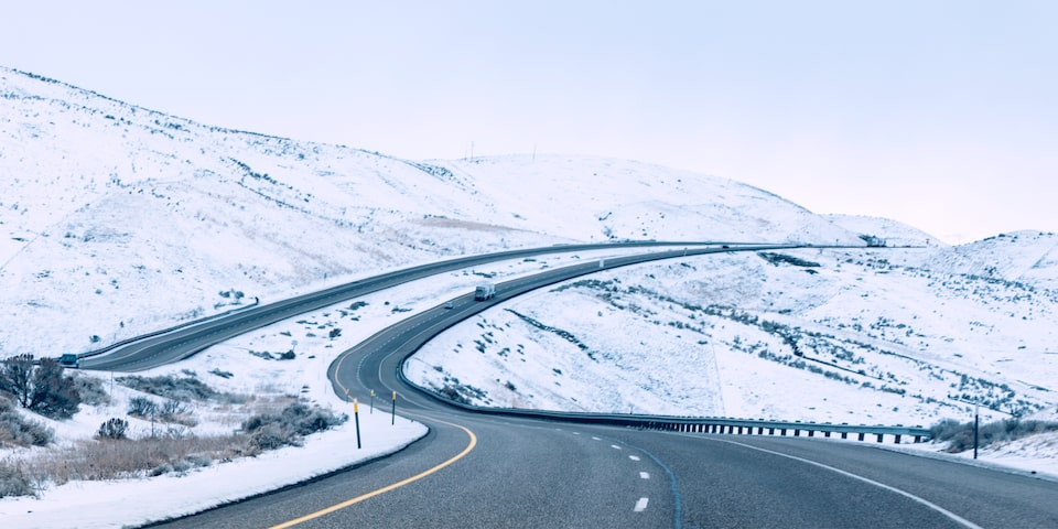 A divided four-lane highway snaking through snow-covered hills.
