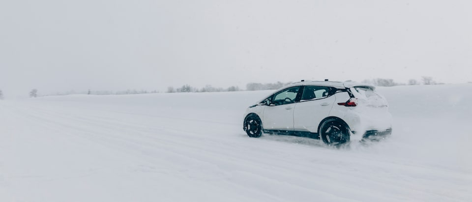A white Chevrolet Bolt EV driving down a flat snow-covered road with no other vehicles in sight and a few trees in the distance.