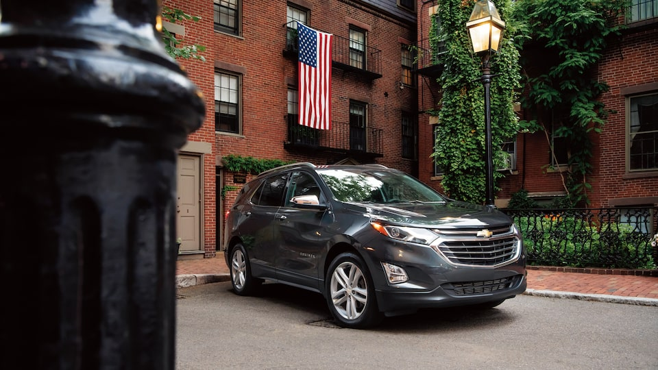 A Chevrolet Equinox parked near a brick building and an American flag.