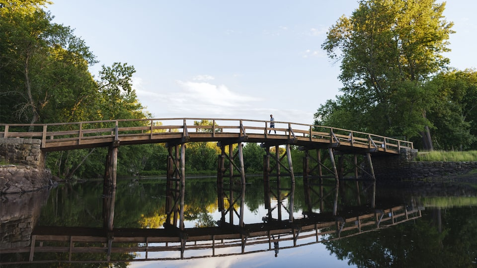 A man walking across Historic North Bridge over the Concord River.