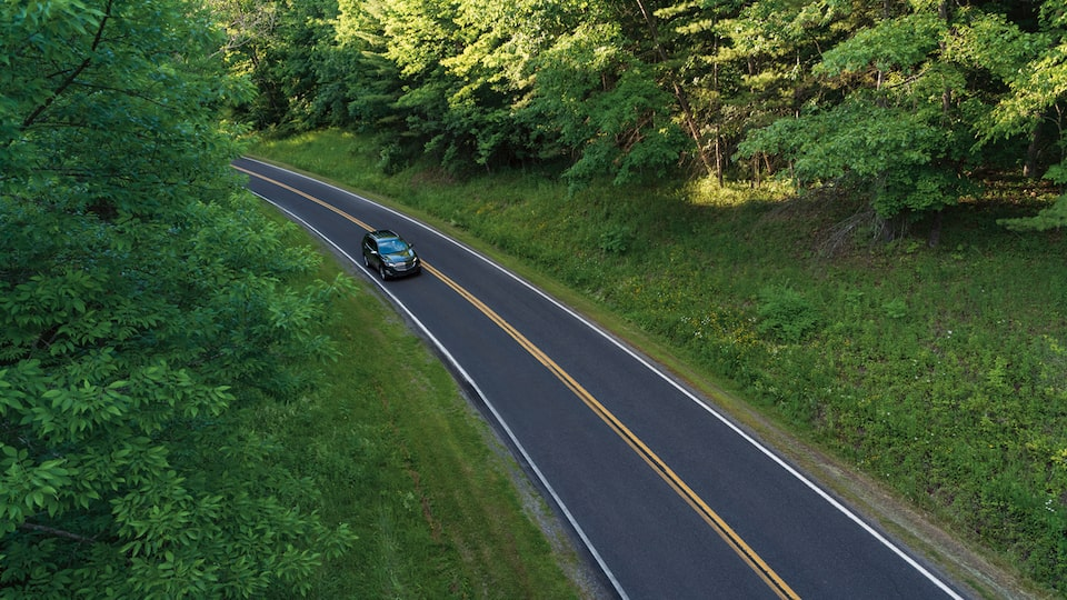 A faraway overhead shot of an Equinox on a two-lane road.