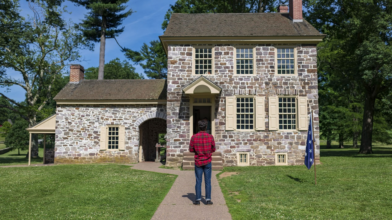 A man in a plaid shirt stands facing an old stone house.