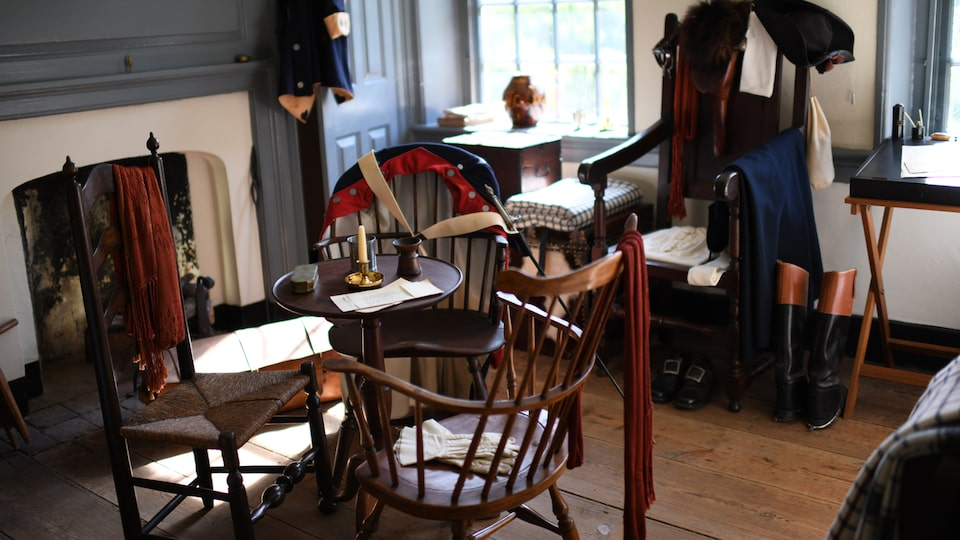 Historic chairs and garments in a living area in Washington's headquarters at Valley Forge.