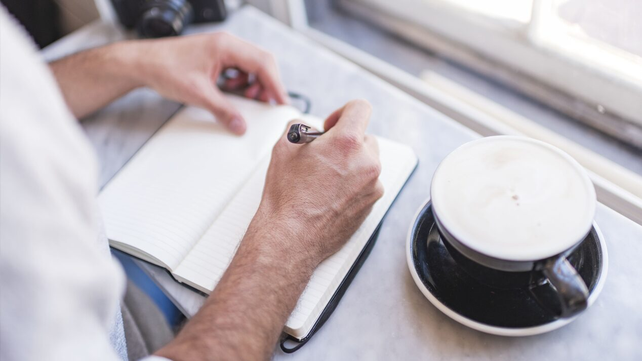 A close-up photo of a man's hands as he writes in his notebook, with a coffee drink on the table.