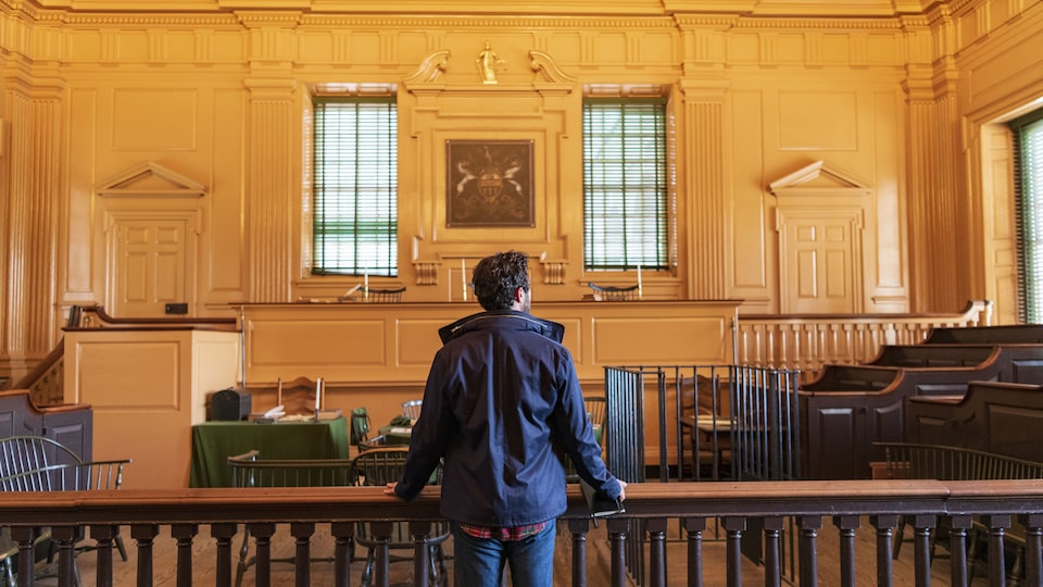 A man stands with his back to the camera inside Independence Hall.