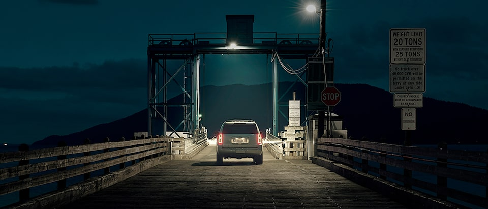 The rear of a Chevy Tahoe SUV as it waits to drive onto a car ferry at night.