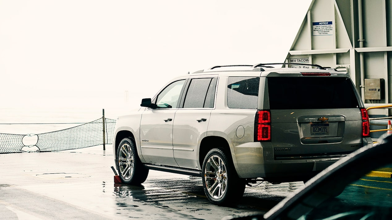 A Chevy Tahoe SUV on the deck of a car ferry, seen from the driver's side rear.