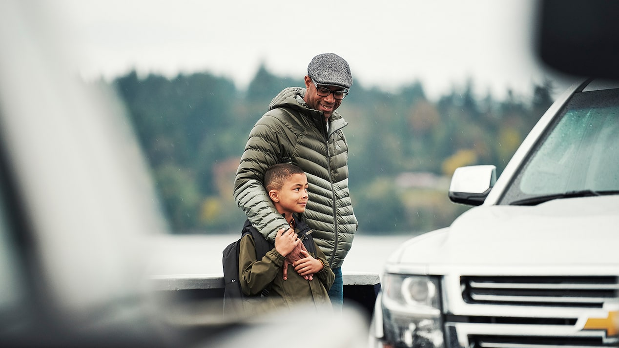 A father with his arm around his son stand on the deck of a car ferry next to a Chevy Tahoe SUV.