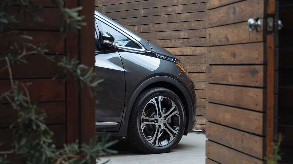 The front end of a dark gray Chevrolet Bolt EV is seen through a wooden doorway.