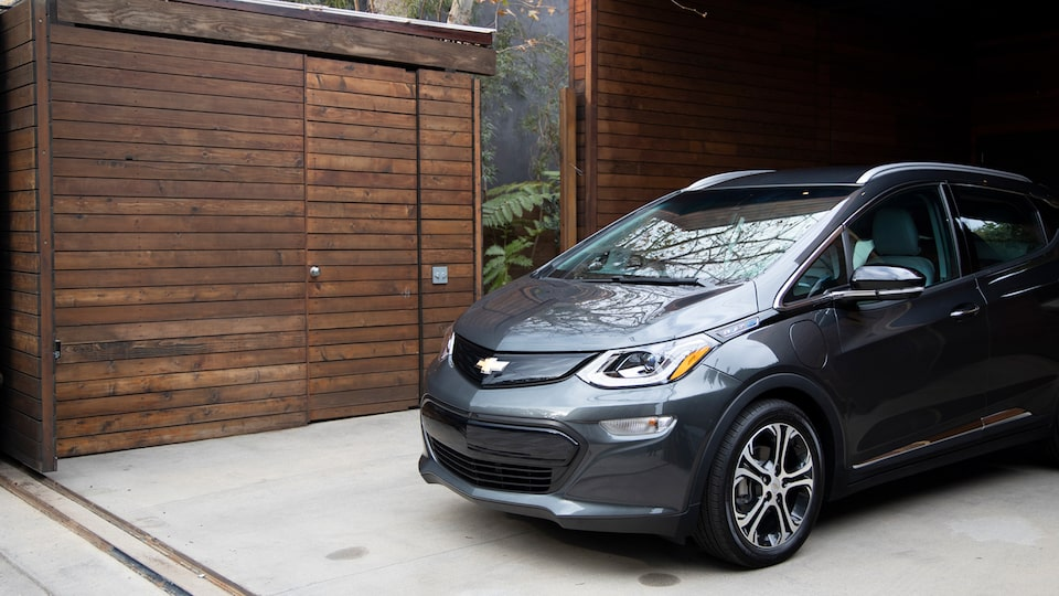 A dark gray Chevrolet Bolt EV coming out of a wooden garage.