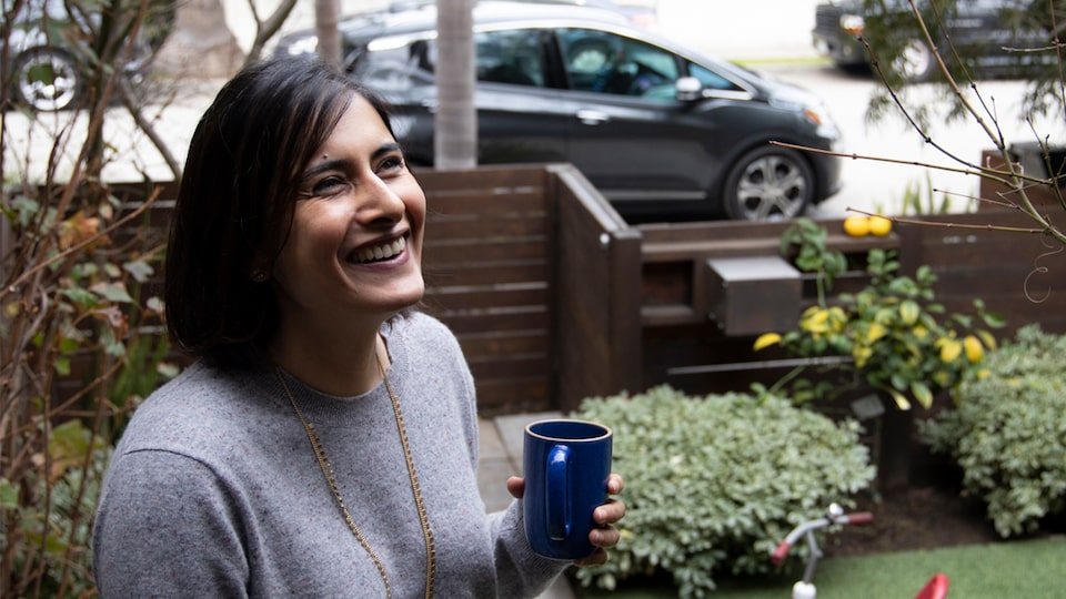 A smiling woman stands in a garden holding a coffee cup, with a dark gray Chevrolet Bolt EV on the street outside the yard.