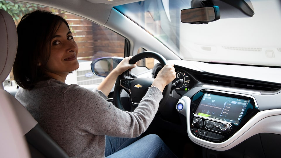 A woman sits in the driver's seat of a Chevrolet Bolt EV and looks back, smiling.