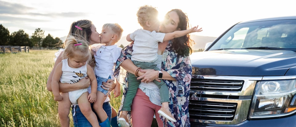 Brittany and Courtney McLachlan hold their children while standing in a field in front of Brittany's Chevrolet Tahoe.