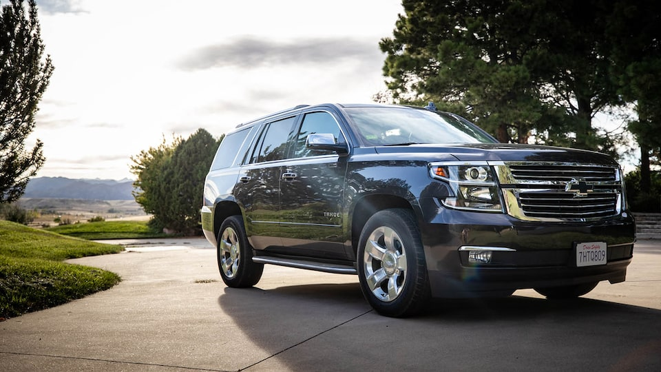 A Chevrolet Tahoe is parked in a driveway with a few trees and other greenery in the background.
