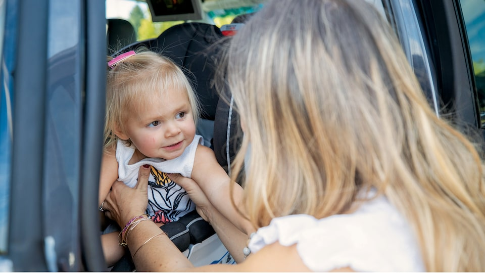 Brittany McLachlan takes her daughter out of her car seat.