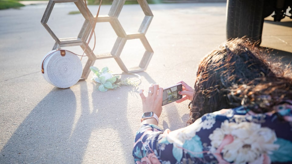 Courtney McLachlan takes a picture of a purse resting against a structure of stacked hexagons.