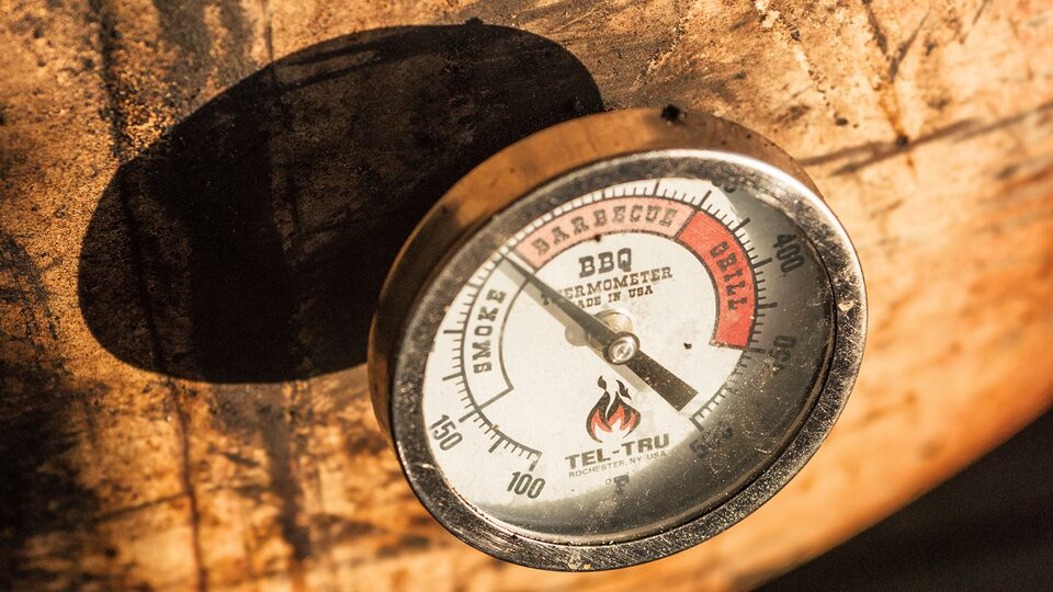 Close-up of a temperature gauge on a smoker.