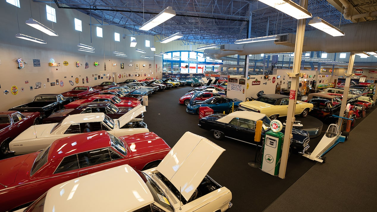A collection of vehicles inside Muscle Car City, including a vintage Impala and a contemporary Corvette.