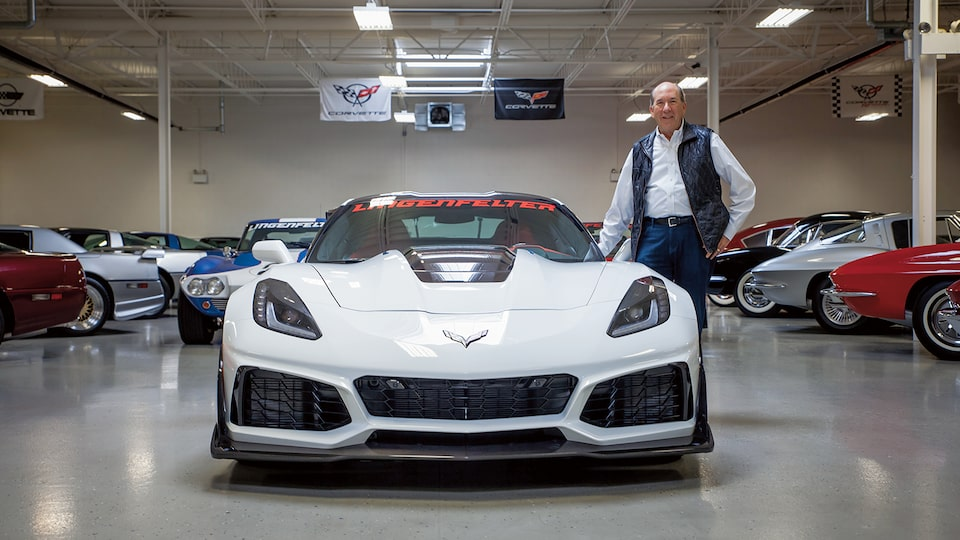 Ken Lingenfelter stands next to a white contemporary Corvette in his collection, with vintage Corvettes in the background.