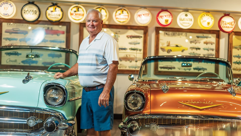 Dennis Albaugh stands in front of two 1950s Chevrolet convertibles, with his hand on one of them.