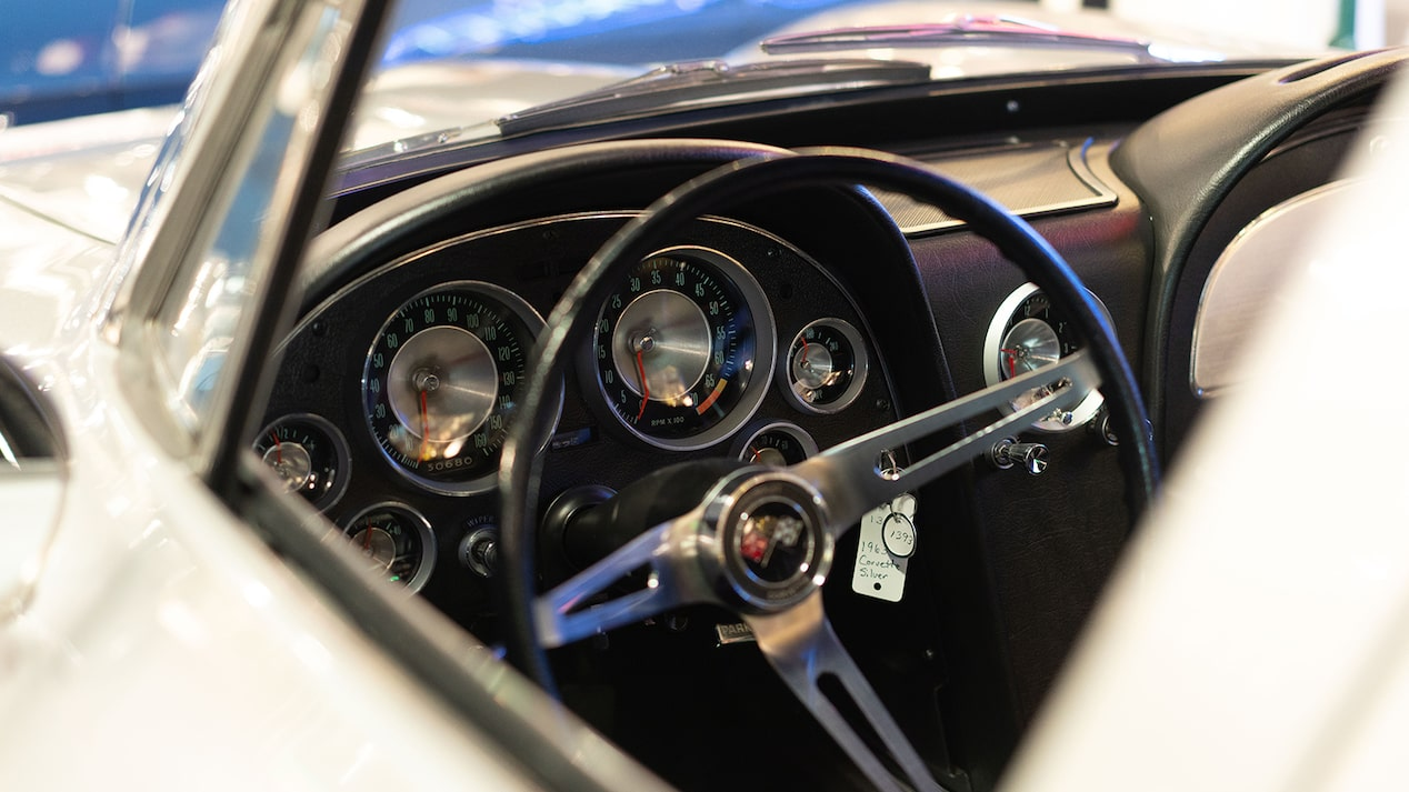 The steering wheel and instrument cluster of a vintage Chevy Corvette.