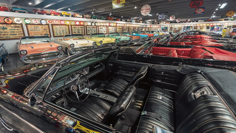 The black interior of a black vintage convertible with 1950s Chevrolet convertibles in the background.