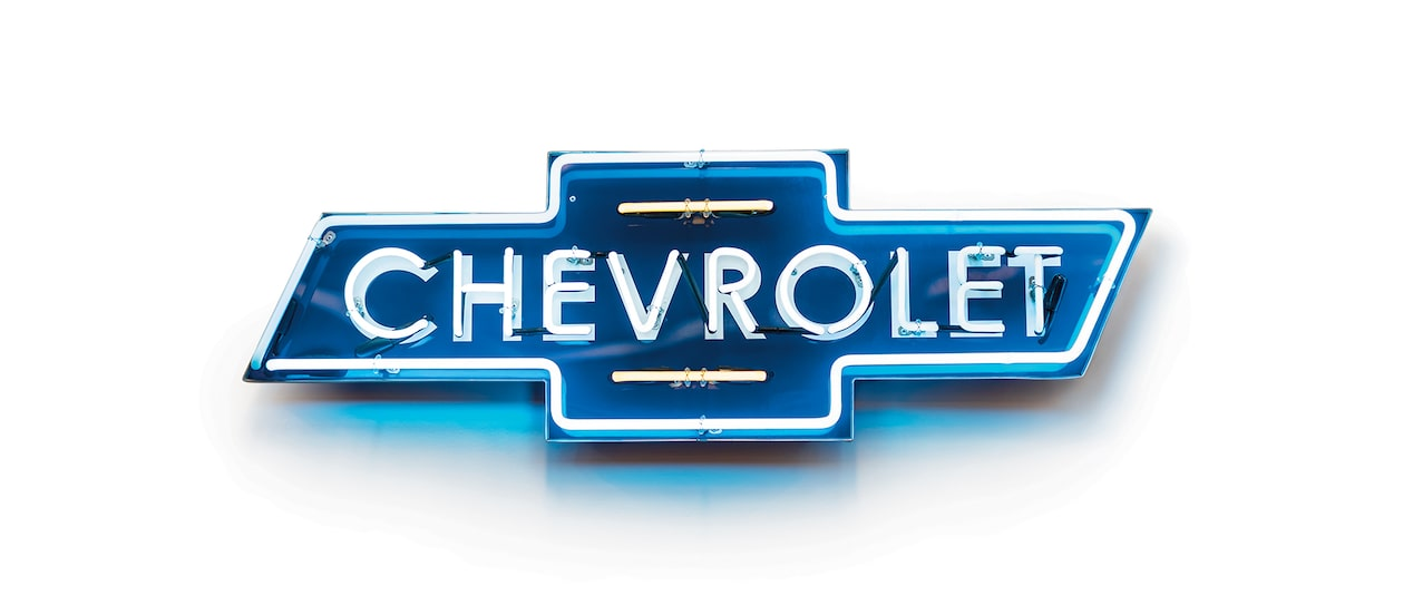 A vintage style blue neon Chevrolet bow tie logo dealership sign.