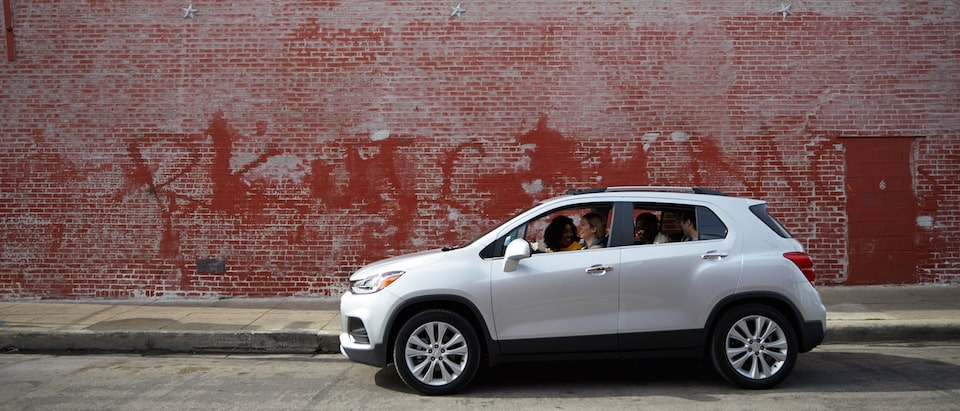 A silver Chevrolet Trax with four occupants sits in front of an old red brick building with faded graffiti on the side.