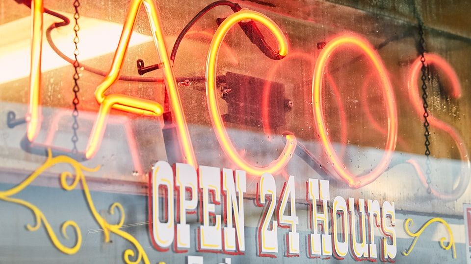 "A red neon sign reads ""Tacos,"" and the window below is painted with the words ""Open 24 hours."""