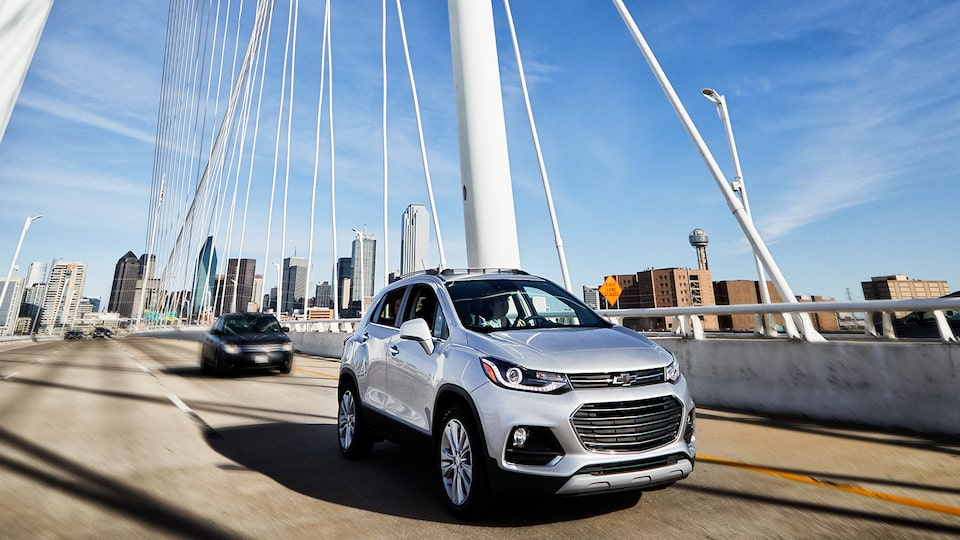 A silver Chevrolet Trax drives across a bridge with the Dallas skyline in the background.