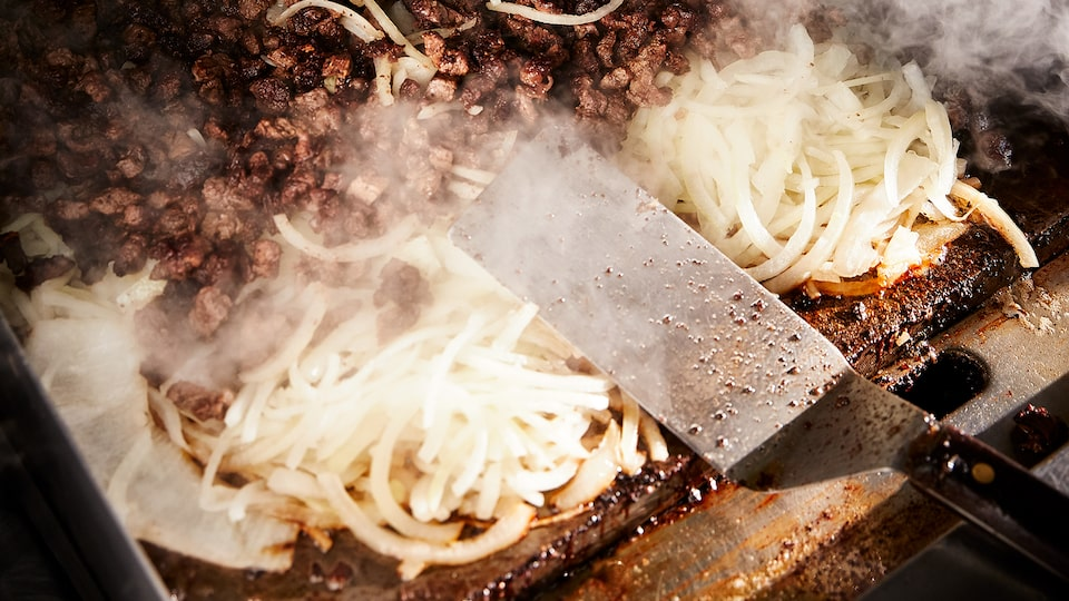 Meat and onions and rising steam on a flat-top grill.