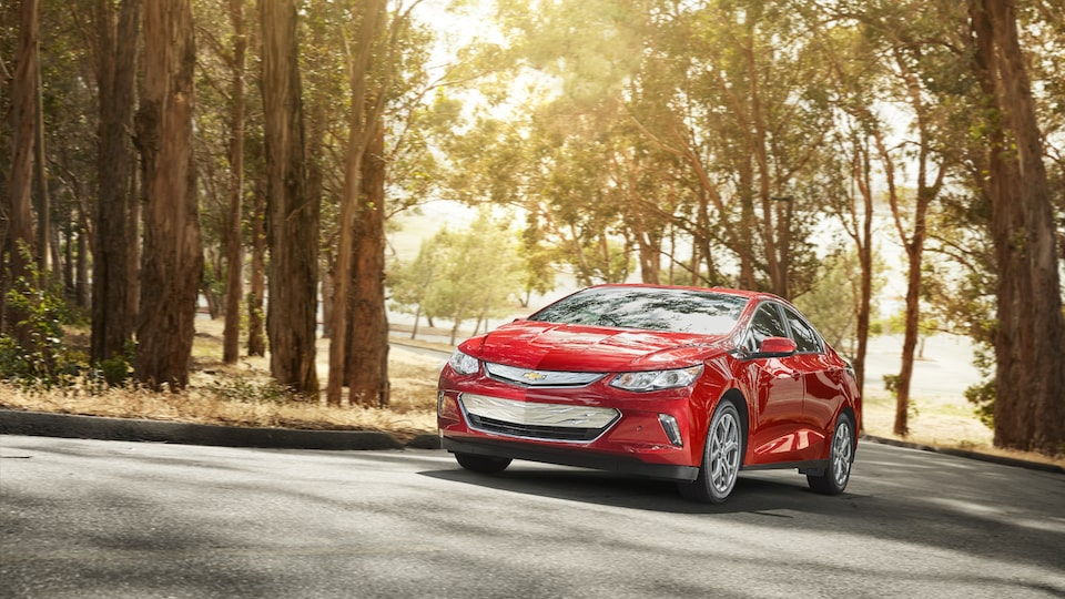 A Chevrolet Volt drives through a curve on a tree-lined road.